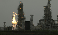 In this April 2, 2010, file photo, a Tesoro Corp. refinery, including a gas flare flame that is part of normal plant operations, is shown in Anacortes, Wash. after a fatal overnight fire and explosion. Voters in Washington state will weigh in on Initiative 732 in the 2016 election as they consider whether to approve the nation's first direct carbon tax on the burning of fossil fuels.