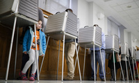 A child waits for her mother to finish voting in a polling booth at the Nativity School on Election Day, Tuesday, Nov. 8, 2016, in Cincinnati. (AP Photo/John Minchillo)