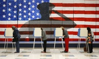 Voters line up in voting booths to cast their ballots at Robious Elementary School in Richmond, Va. on Tuesday, Nov. 8, 2016. The mural in the background was painted by 3rd and 4th graders at the school in preparation for Veterans Day.