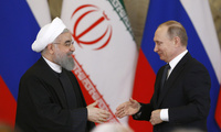 Russian President Vladimir Putin, right, shakes hands with Iranian President Hassan Rouhani