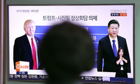 "A woman watches a TV news program reporting about the first summit between U.S. President Donald Trump, left, and Chinese President Xi Jinping, at Seoul Train Station in Seoul, South Korea, Thursday, April 6, 2017. The letters read ""Summit, Donald Trump - Xi Jinping."" (AP Photo/Lee Jin-man)"