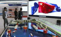 Visitors look at the models of oil tanker shaped floating nuclear reactors and oil rigs showcased at the display booth of China's state-owned China National Nuclear Corporation during the China International Exhibition on Nuclear Power Industry in Beijing. April 27, 2017 (Andy Wong/Associated Press).