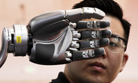 A visitor looks at a robotic hand powered by Kinfinity Glove, developed by the German Aerospace Center, on display at the World Robot Conference at the Yichuang International Conference and Exhibition Centre in Beijing, Wednesday, Aug. 23, 2017.