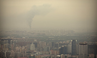 Smoke rises above the skyline of Beijing on a moderately polluted day, Saturday, Aug. 26, 2017. (AP Photo/Mark Schiefelbein)