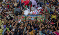 Rohingya Muslims, who crossed over from Myanmar into Bangladesh, stretch their arms out to collect food items distributed by aid agencies near the Balukhali refugee camp in Bangladesh on Sept. 18, 2017. (AP Photo/Dar Yasin)