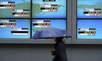 A woman walks past an electronic stock board showing Japan's Nikkei 225 index and other county's index at a securities firm in Tokyo on Monday, October 16, 2017. (AP Photo/Eugene Hoshiko)