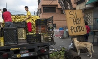 "Workers prepare to unload banana boxes at a popular market in Caracas, Venezuela on Wednesday, Oct. 25, 2017. The sign on the right reads in Spanish ""There is point,"" referring to the possibility of paying by card due to the lack of cash from the ongoing economic crisis. (AP Photo/Rodrigo Abd)"