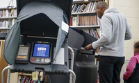 A voter casts his ballot into an electronic voting machine at a polling station located in the Taft Information Technology High School in Cincinnati. November 7, 2017 (John Minchillo/Associated Press). Keywords: electronic voting machine, Cincinnati