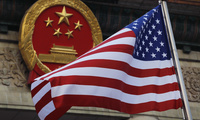An American flag is flown next to the Chinese national emblem during a welcome ceremony for visiting U.S. President Donald Trump outside the Great Hall of the People in Beijing. November 9, 2017 (Andy Wong/Associated Press).
