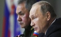 Russian President Vladimir Putin, foreground, Russian Defense Minister Sergei Shoigu, attend a meeting while visiting the Military Academy of Strategic Rocket Troops of the Peter the Great in Balashikha, outside Moscow on December 22, 2017.