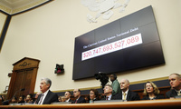 The National debt is shown behind Federal Reserve Chairman Jerome Powell, left, as he makes the semiannual monetary policy report to the House Financial Services Committee, February 27, 2018, in Washington. (AP Photo/Jacquelyn Martin)