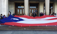 Activists hold up a flag of the U.S. territory of Puerto Rico, which was devastated by Hurricane Maria in September, during a protest outside the Connecticut state Capitol on Wednesday, Feb. 28, 2018. (AP Photo/Susan Haigh)