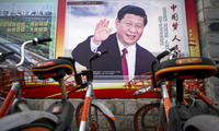 Shared bicycles are parked near a propaganda billboard showing Chinese President Xi Jinping along a street in Beijing. March 2, 2018 (Mark Schiefelbein/Associated Press). Keywords: Xi Jinping, China, Beijing