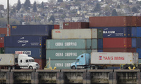 "Trucks pass by cargo containers labeled ""China Shipping"" at the Port of Seattle. April 6, 2018 (Ted S. Warren/Associated Press). China, shipping, tariffs, trade"