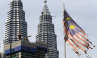 A battered Malaysian national flag flies in front of the Petronas Towers in Kuala Lumpur, Malaysia on Tuesday, April 10, 2018. (AP Photo/Vincent Thian)