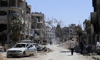 Syrians walk through destruction in the town of Douma, the site of a suspected chemical weapons attack, near Damascus, Syria. April 16, 2018 (Hassan Ammar/Associated Press). Keywords: Syria, chemical weapons attack, Douma