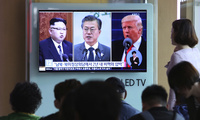 Commuters watch file footage of U.S. President Donald Trump, right, South Korean President Moon Jae-in and North Korean leader Kim Jong Un, left, on a public television at Seoul Railway Station in Seoul, South Korea on Wednesday, April 18, 2018. (AP Photo/Ahn Young-joon)