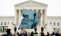 "A person holding a sign that reads ""No Muslim Ban"" in front of the Supreme Court"