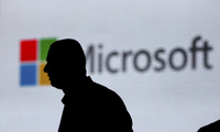 In this Nov. 7, 2017, file photo, an unidentified man is silhouetted as he walks in front of Microsoft logo at an event in New Delhi, India. Microsoft says it's committing to giving users worldwide the same data and privacy rights being offered to Europeans under new regulations there. That means no matter where you live, you'll be able to see what Microsoft collects about you and correct or delete that information if necessary.
