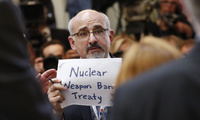 "A man holds a sign that reads ""Nuclear Weapons Ban Treaty""prior to a press conference during the Helsinki Summit with Trump and Putin."