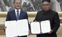 In this image made from video provided by Korea Broadcasting System (KBS), South Korean President Moon Jae-in, left, and North Korean leader Kim Jong Un pose after signing documents in Pyongyang on Sept. 19, 2018 (Korea Broadcasting System via AP).