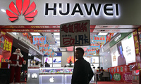 A worker holds a sign promoting a sale for Huawei 5G internet services at a mobile phones retail shop in Shenzhen in south China's Guangdong province, Tuesday, Dec. 18, 2018. The chairman of Huawei challenged the United States and other governments to provide evidence for claims the Chinese tech giant is a security risk as the company launched a public relations effort Tuesday to defuse fears that threaten its role in next-generation communications.