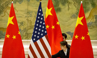 Photo of Chinese staffers adjust U.S. and Chinese flags before the opening session of trade negotiations between U.S. and Chinese trade representatives at the Diaoyutai State Guesthouse in Beijing, Thursday, Feb. 14, 2019.
