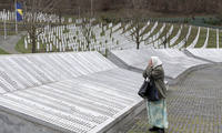 A woman prays at the Potocari memorial in Bosnia and Herzegovina