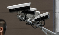 People walk by Chinese-made surveillance cameras.