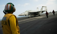 Crew member looks at a taxing F/A-18 fighter jet on the deck of the USS Abraham Lincoln aircraft carrier