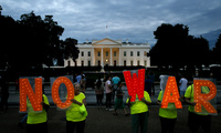 "Protesters hold up letters that spell out ""No War"" outside the White House"