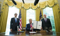 President Donald Trump, accompanied by Treasury Secretary Steve Mnuchin and Vice President Mike Pence, holds up a signed executive order to increase sanctions on Iran on June 24.