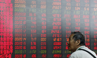 A man monitors stock prices at a brokerage house in Beijing.