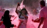 A runner passes through clouds of colored powder during the Color Run, also known as the Happiest 5k on the Planet, in Jiddah, Saudi Arabia