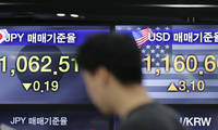 A currency trader stands by the screens showing the foreign exchange rates at the foreign exchange dealing room in Seoul, South Korea, Friday, Nov. 8, 2019.