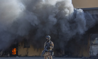 An Iraqi soldier stands guard in front of smoke rising from a fire in the U.S. embassy compound , in Baghdad, Iraq.