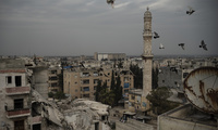 A mosque stands next to a a damaged building, in Idlib, Syria.