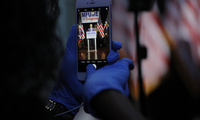 A staff member in the Kweisi Mfume campaign uses gloves while holding a cell phone during an election night news conference at his campaign headquarters after Mfume, a Democrat, won Maryland's 7th Congressional District special election, Tuesday, April 28, 2020, in Baltimore.