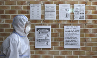 A health official wearing protective gear walks near banners showing precautions against the new coronavirus ahead of school reopening in a cafeteria at a high school in Seoul, South Korea.