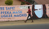 A young boy walks past a wall with graffiti urging people to wear face masks in Harare, Thursday, May, 28, 2020.