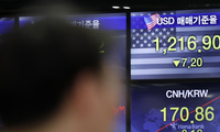 A currency trader works near the screens showing the foreign exchange rates at the foreign exchange dealing room in Seoul, South Korea, Thursday, June 4, 2020.