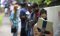 Photo of Kelsey Luker reading as she waits in line to vote, Tuesday, June 9, 2020, in Atlanta. Luker said she had been in line for almost two hours.