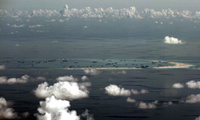 This photo taken through a glass window of a military plane shows China's alleged on-going reclamation of Mischief Reef in the Spratly Islands in the South China Sea on Monday, May 11, 2015. As China builds artificial islands in a vast resource-rich South China Sea, neighbors in Southeast Asia brace for possible conflict.(Ritchie B. Tongo/Pool Photo via AP)