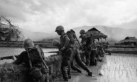 "U.S. Marines pause on the banks of a dike in a rice paddy in the Viet an Valley, which they have dubbed ""Death Valley,"" 350 miles northeast of Saigon, December 15, 1965. In the big joint operation ""Harvest Moon,"" south of Da Nang, marines and Vietnamese soldiers have been trying to trap a major Viet Cong force. Across the dike a Vietnamese house burns. (AP Photo)"