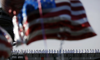Sailors line up on U.S. navy nuclear-powered aircraft carrier USS Ronald Reagan as some U.S. flag-shaped balloons are hoisted to welcome them at the U.S. Navy's Yokosuka base in Yokosuka, south of Tokyo, October 1, 2015. (AP Photo/Eugene Hoshiko)