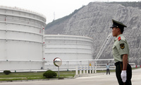Security guards watch near oil tanks at Zhoushan Oil Reserve in Zhoushan in Zhejiang Province, China, June 3, 2009.