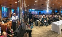 An overflow crowd listens to a panel discussion on the background and impact of Russian cyber attacks. (Bennett Craig)