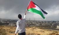 A young man waves the Palestinian flag.