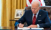 President Biden signing executive orders in the Oval Office on Jan. 21, 2021.