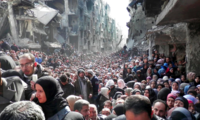 Residents of the Palestinian refugee camp of Yarmouk, lined up to receive food supplies, in Damascus, Syria, in 2014.